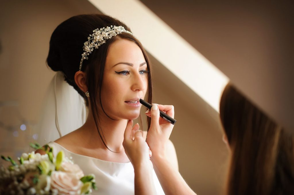 bride having make up applied on lips