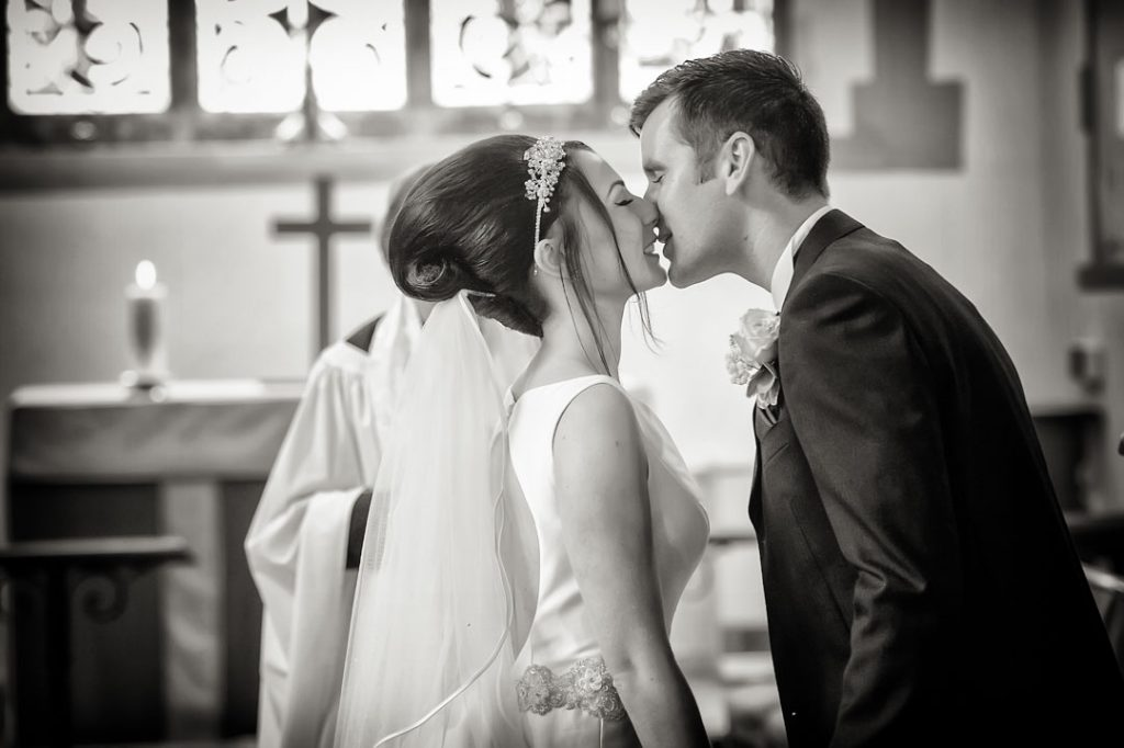 bride kissing groom at the alter