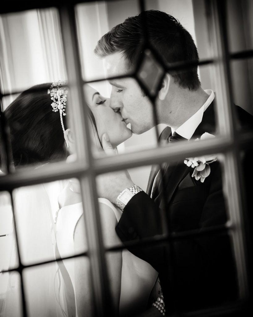 bride and groom kisses through window