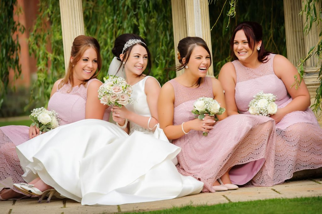 bridesmaid in pink dresses sat on floor