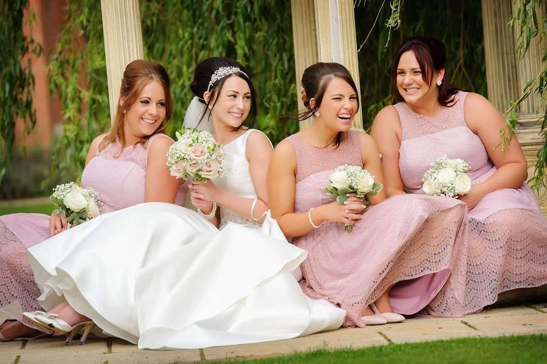 bridesmaid in pink dresses sat on floor