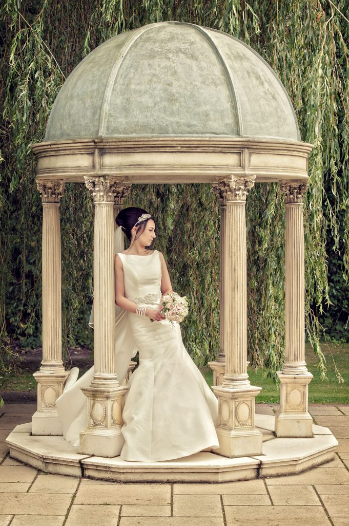 bride leans on outdoor gazebo at the dower house hotel