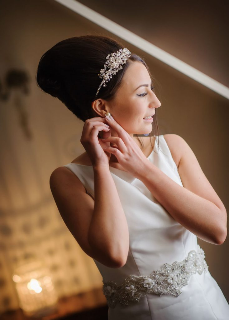 bride in white dress adjusting earrings