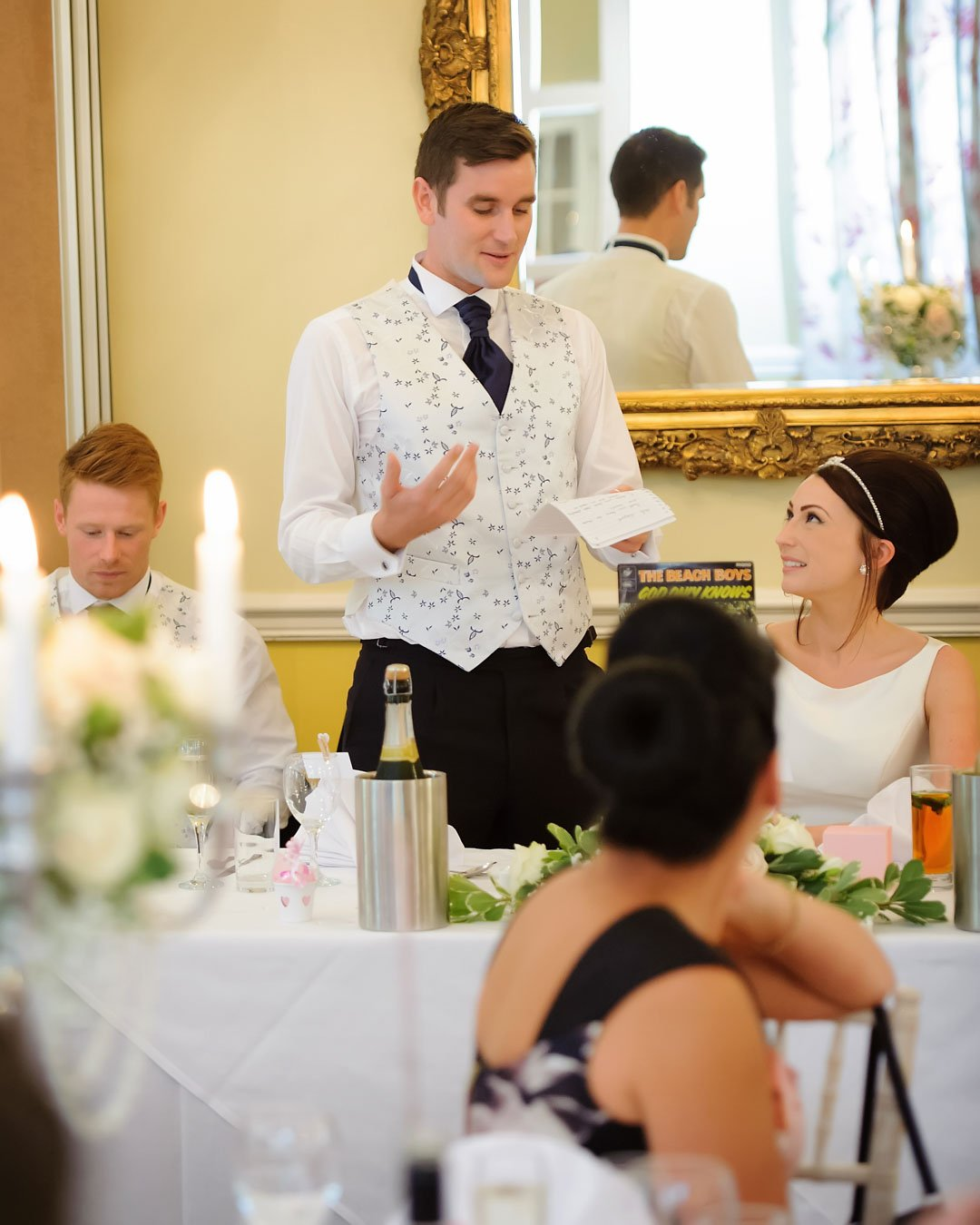 man stands to talk to bride