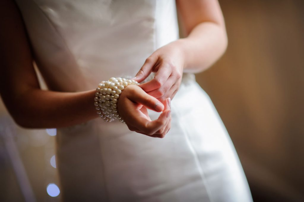 bride adjusting wedding beads on wrist