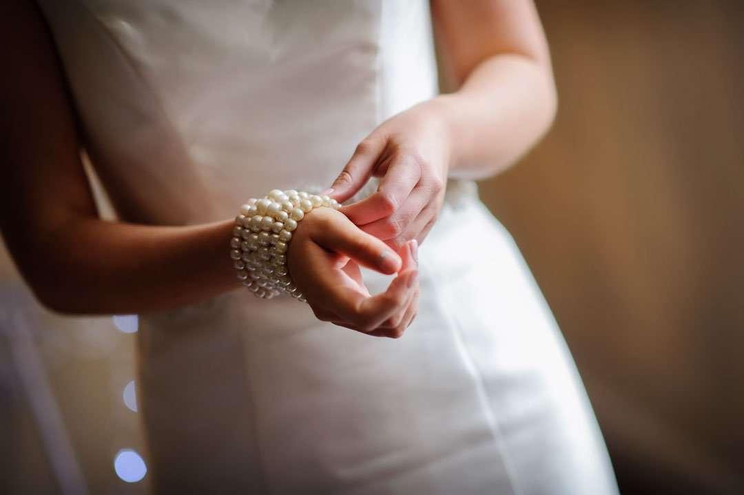 bride adjusting wedding beads on wrist