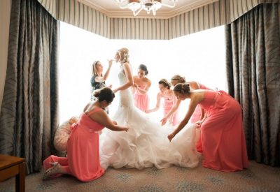 bridesmaids helping bride into wedding dress
