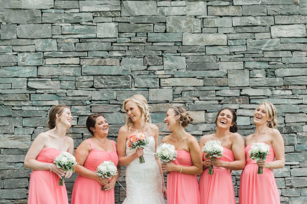 bridesmaids laughing holding flowers