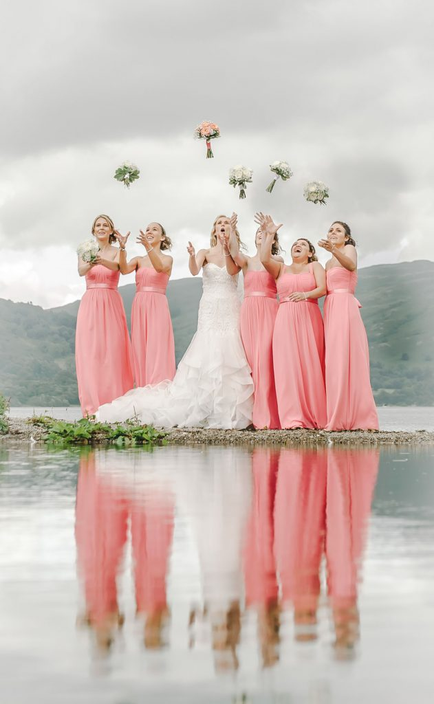 bride and bridesmaids throw wedding flowers