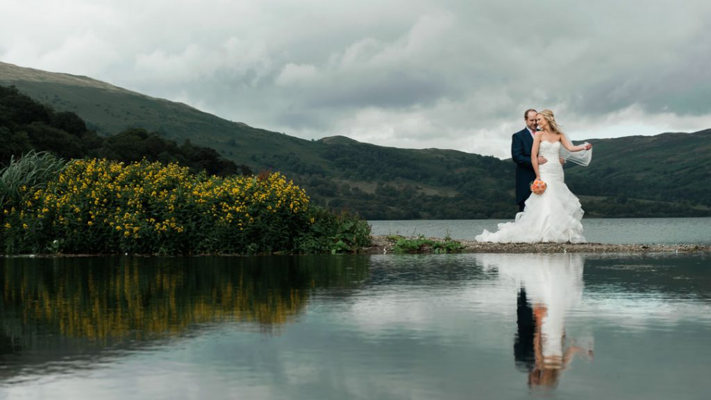 bride and groom showing in reflection near lake in outdoor wedding