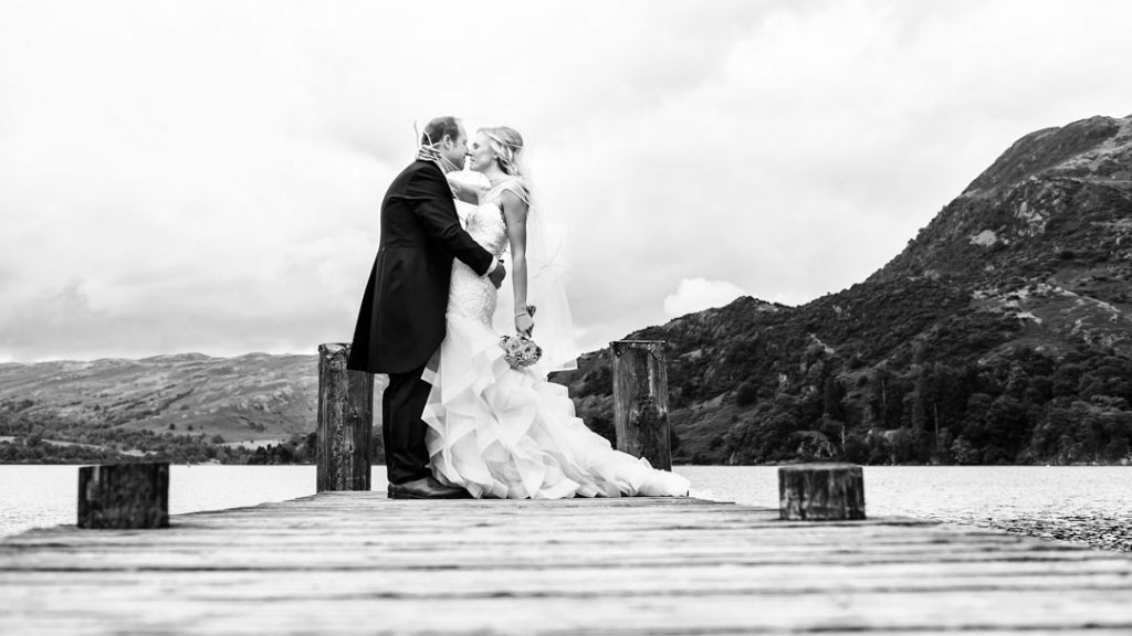 bride and groom kiss in romantic outdoor wedding