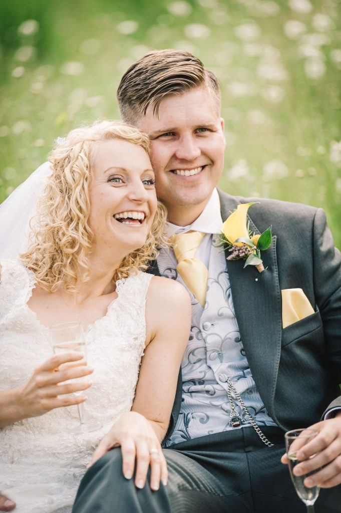 bride and groom laughing sat on haystack