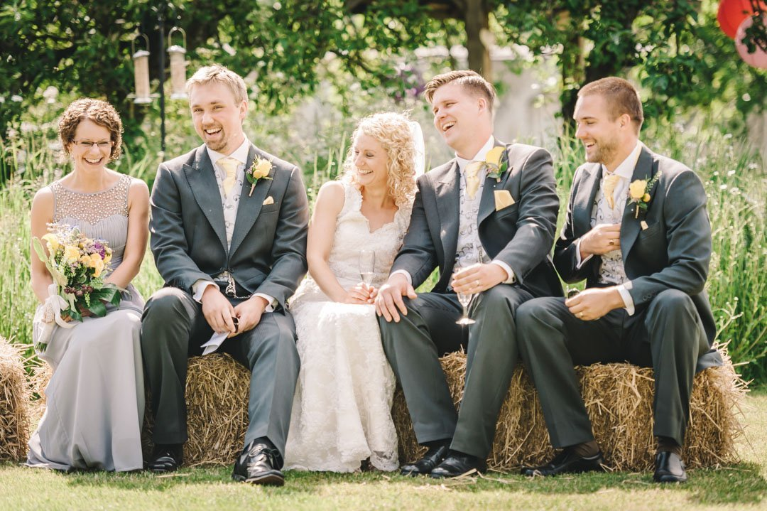 wedding party sat on haystack at scrivelsby walled garden