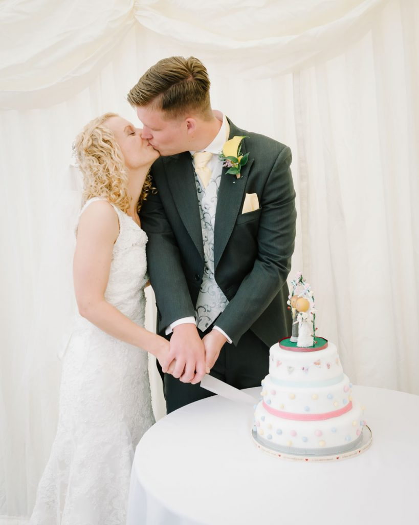 bride and groom kiss whilst cutting wedding cake