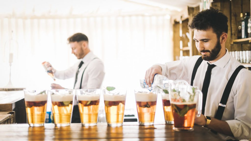 bar tender pouring drinks at marquee wedding
