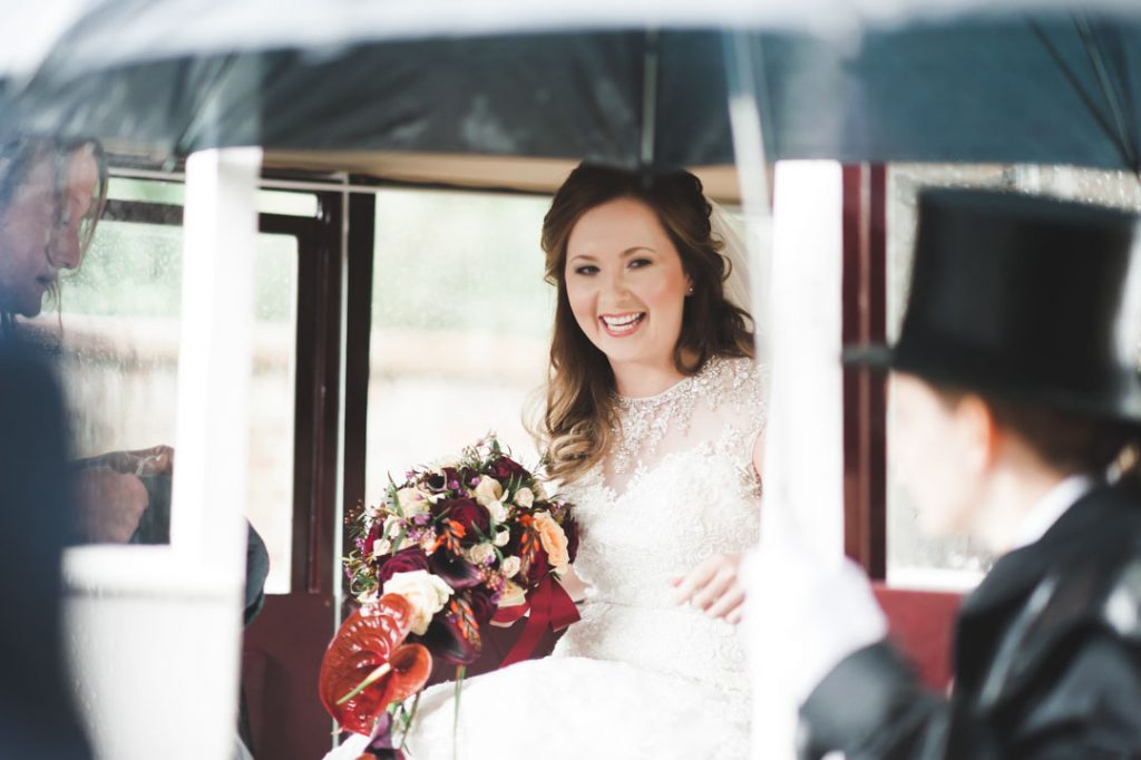bride exiting horse drawn carriage