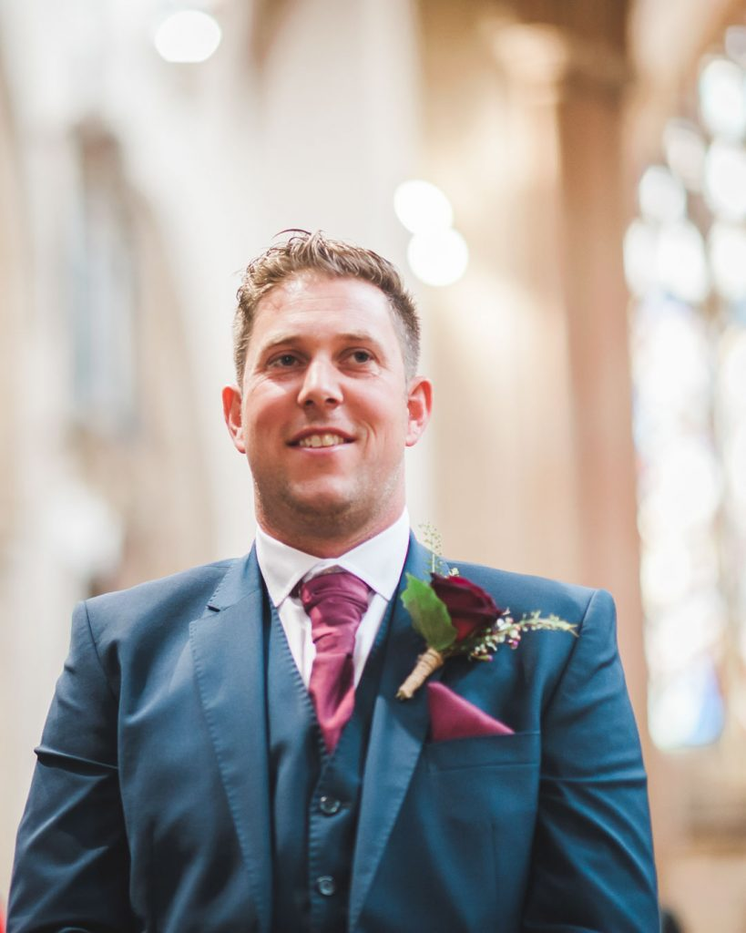 groom in blue suit waiting for bride at isle