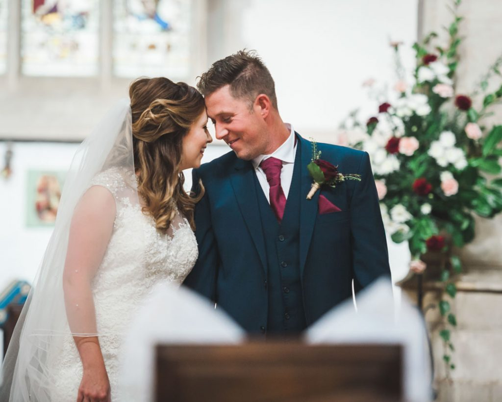 bride and groom touching foreheads inside louth church