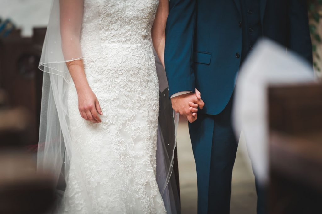 close up of groom holding brides hand