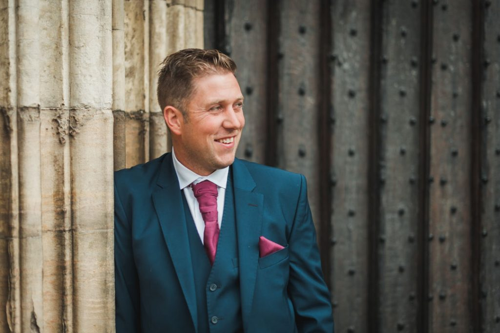 groom posing outside st James church