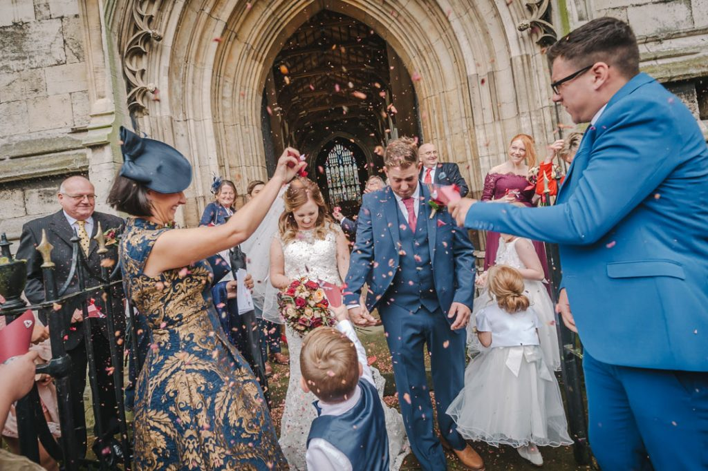 guests throwing confetti over bride and groom st James church louth