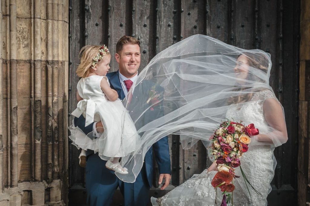 brides veil blown across face outside st James church louth
