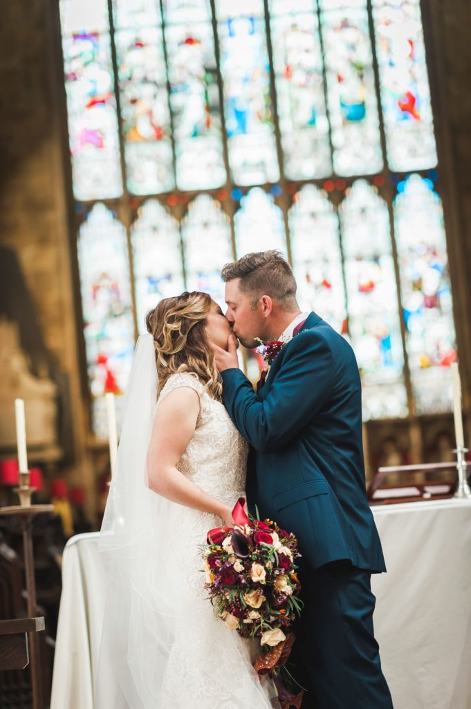 bride at alter kissed by groom