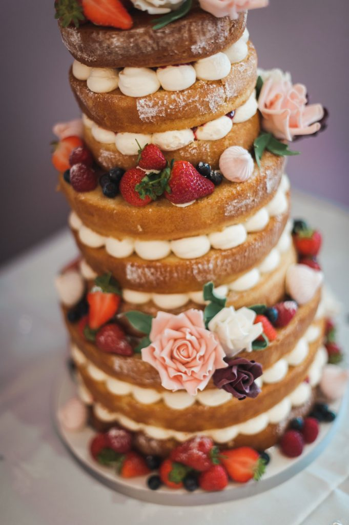 sponge wedding cake with strawberries at wedding reception