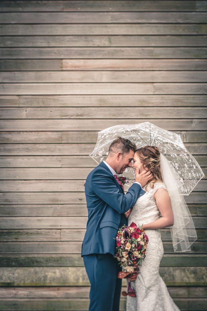 groom holding brides face with umbrella louth wedding