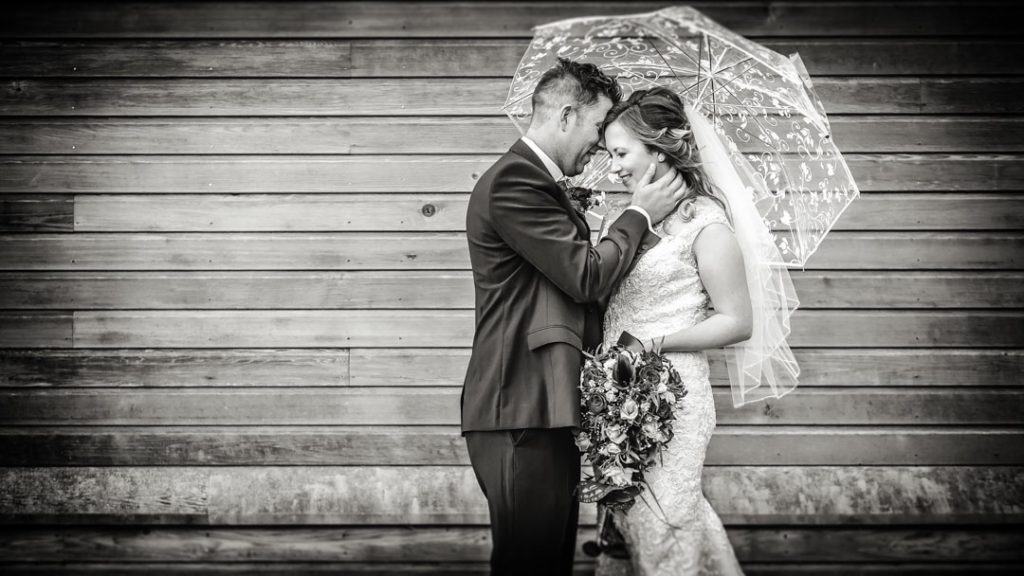 bride holding umbrella with groom black and white