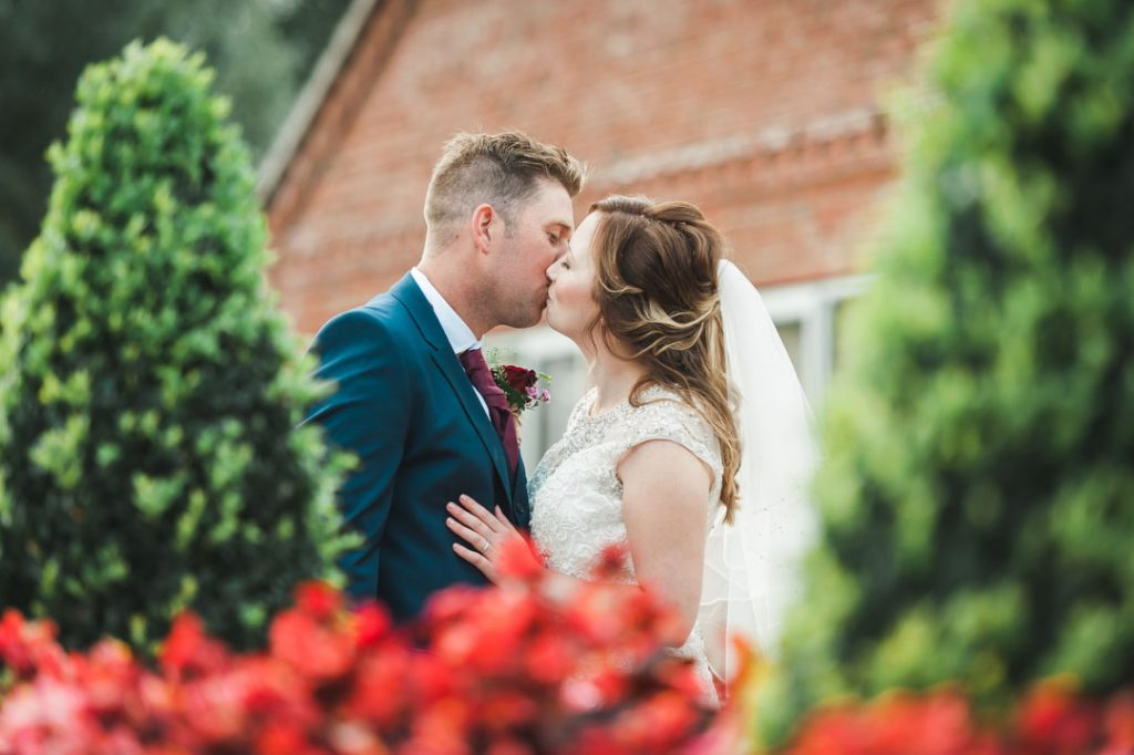 bride kisses groom outside of woodys woodthorpe