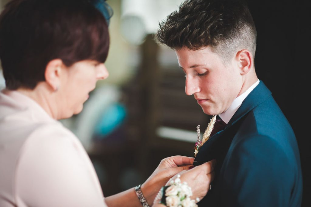 guests at wedding putting on button hole flower