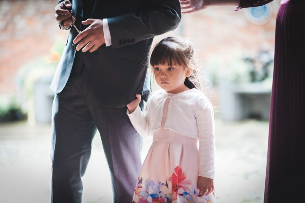 small child at wedding holding fathers suit