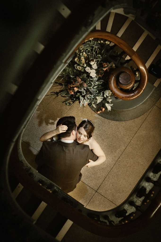 bride and groom embrace on stairs