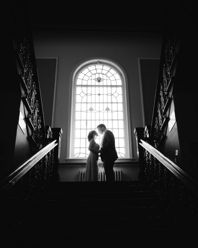 silhouette of bride and groom next to window