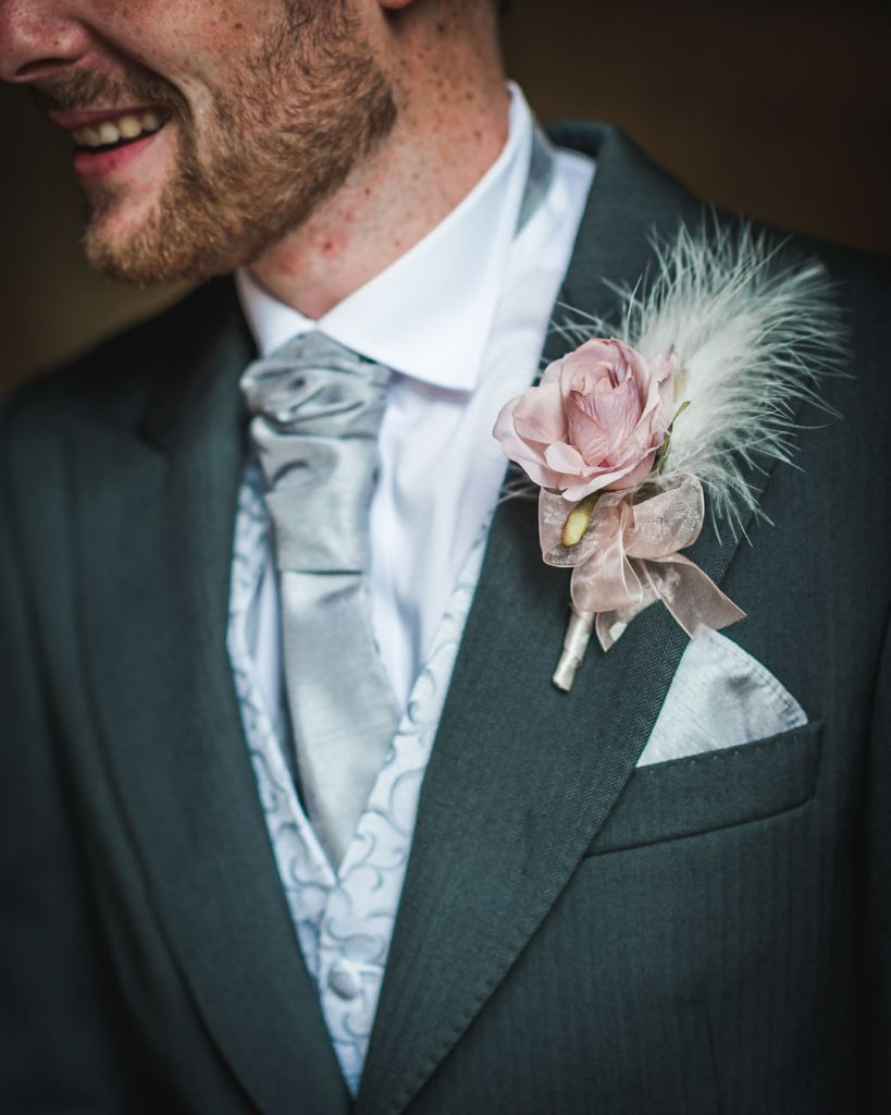 groom in grey suit and pink flower