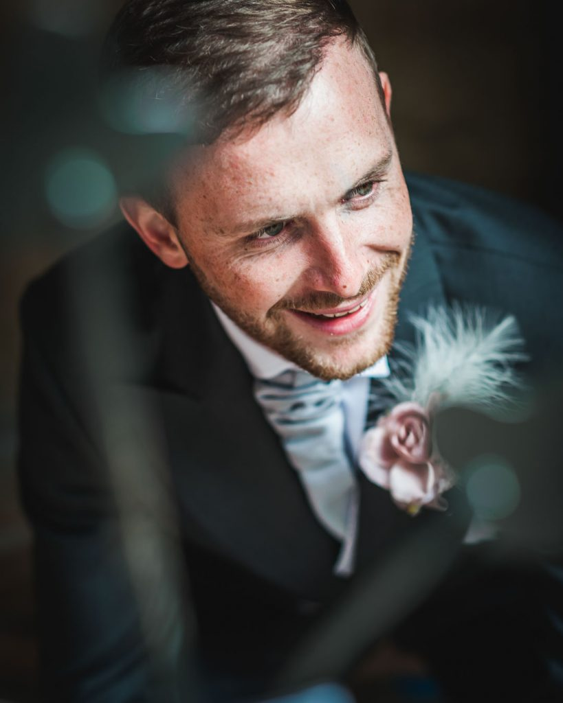 groom with grey suit and pink flower