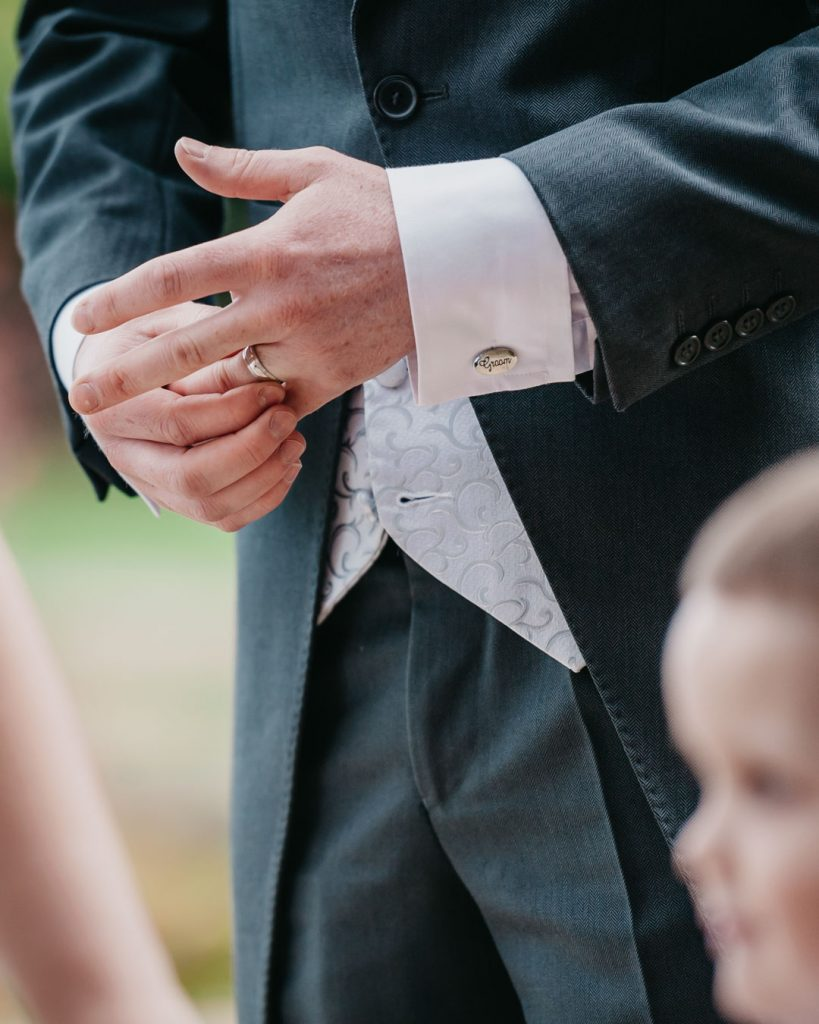 groom plays with wedding ring on finger