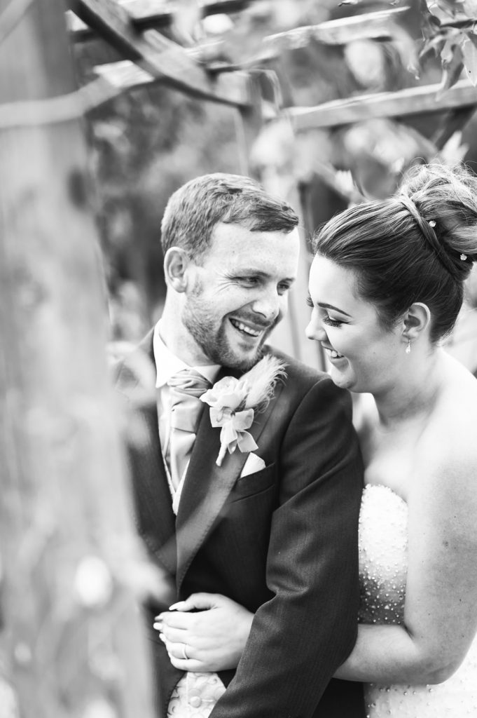 bride laughs at groom black and white