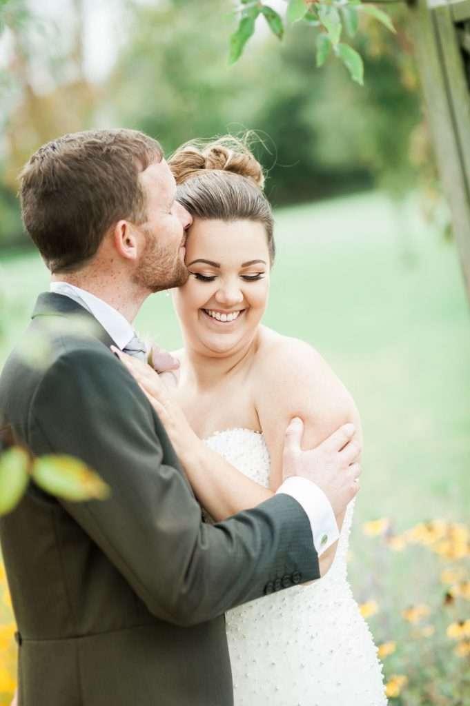 groom kisses temple of bride