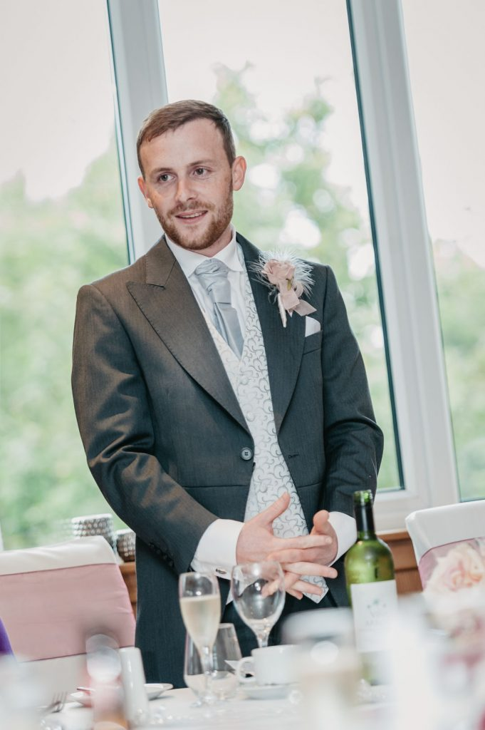 groom stands in grey suit grimsby laceby manor