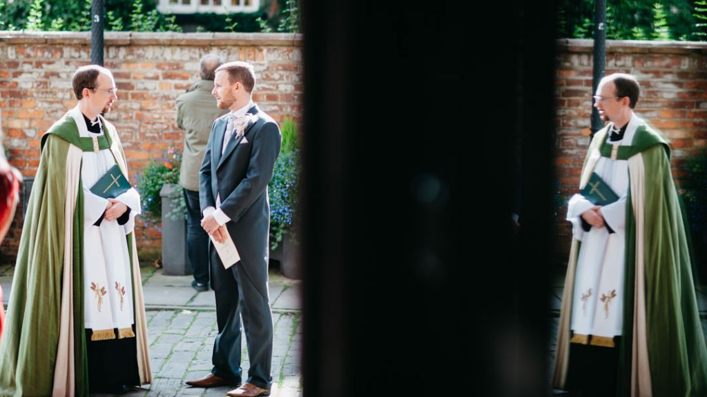 groom talks with vicar outside church