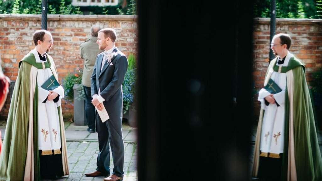 groom talks with vicar outside church