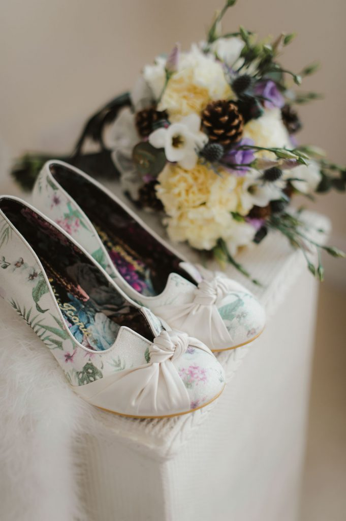 wedding shoes next to yellow wedding flowers