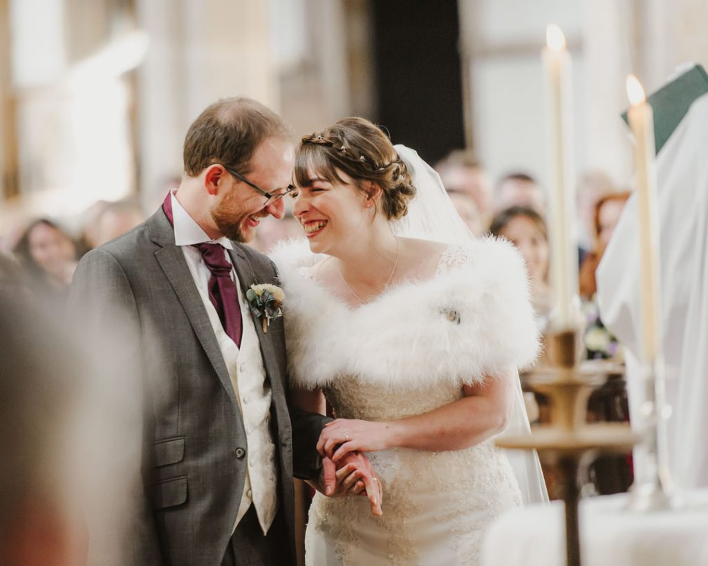 bride and groom laugh at church ceremony