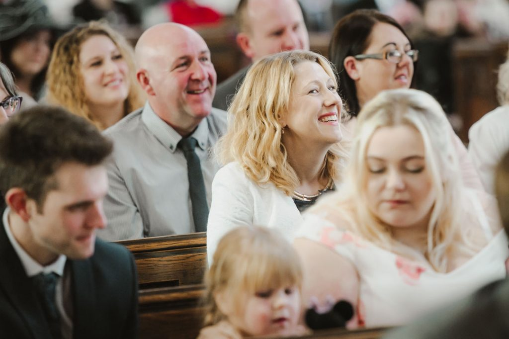 wedding guest smiling in white top
