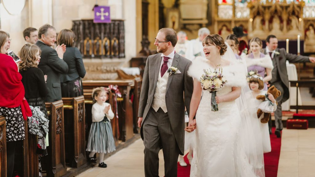 bride in white dress walking down the isle