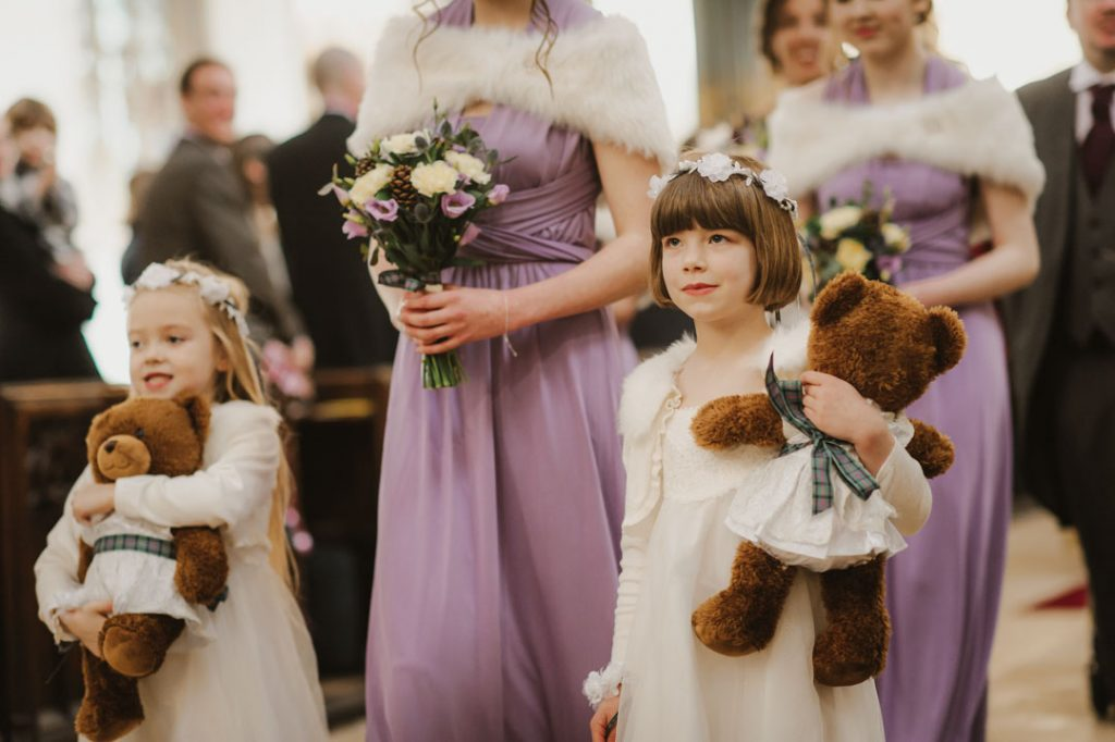 bridesmaid in white dress holding teddy bear
