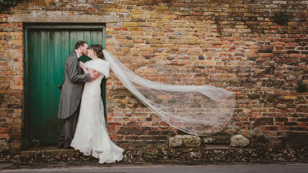 bride and groom stood against green door and wall
