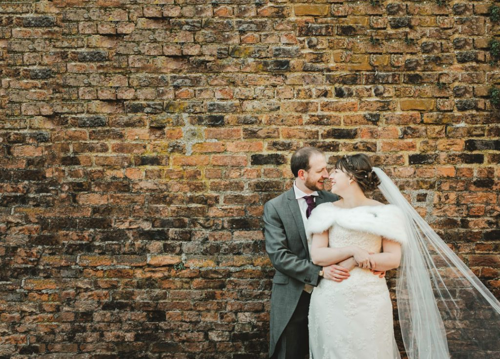 bride and groom stood against brick wall urban wedding photography